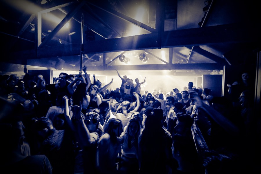 large group of people dancing and drinking at a dark nightclub