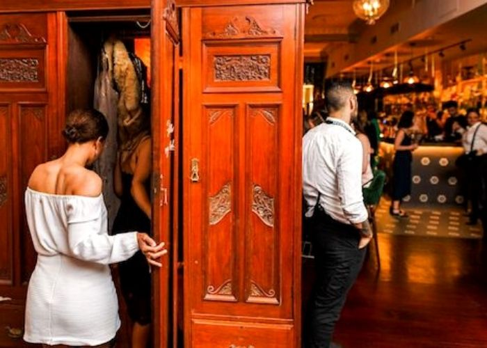 Woman in white dress stepping into wardrobe in Trinket bars hidden cellar bar with bar tender and people drinking in back ground