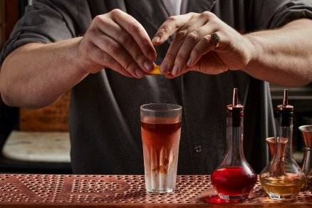 male bar tender squeezing lemon into cocktail drink at bar