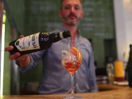 bar tender pouring cocktail at bar