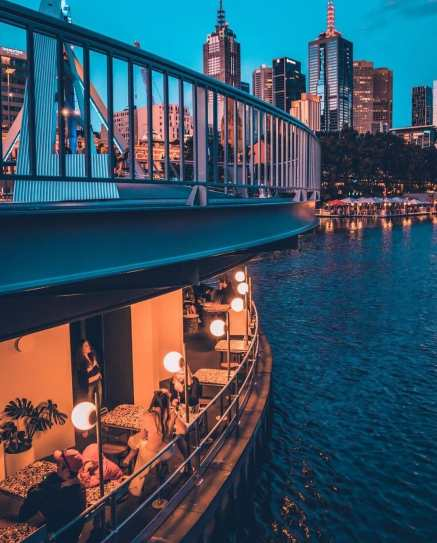 yarra pedestrian bridge curving with diners eating at restaurant below with glowing lights above the river