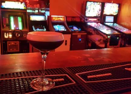 espresso martini cocktail on bar with retro arcade games in background