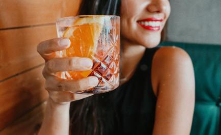 woman smiling in green dress holding glass of nagroni with orange slice