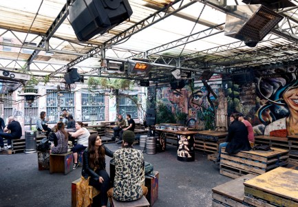 patrons on wooden pallet seating under clear roof at section 8 melbourne