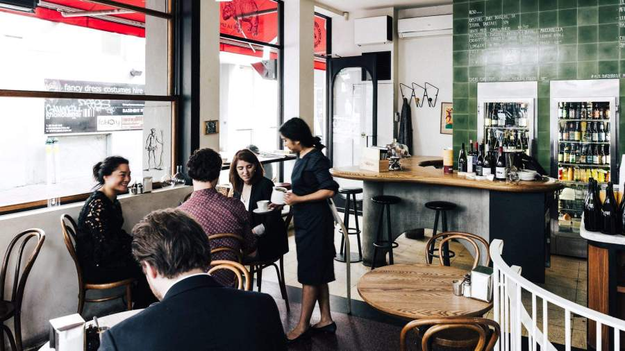 waitress serving seated patrons coffee at kirks wine bar with wine bottles in back ground and green tiles