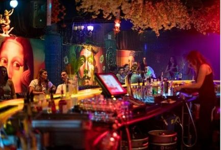 miranda night club with bar staff making drinks and people drinking in booths and lounges