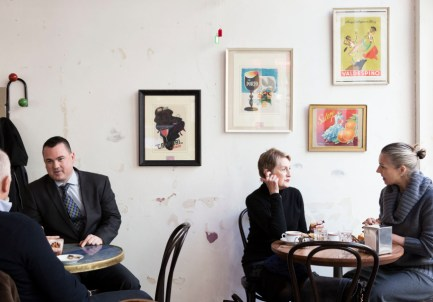 two woman seated and having coffee with two men at diffrent table in suits eating breakfast
