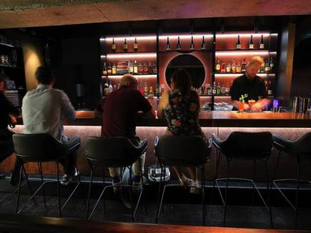 patrons seated in black stools at bar with bar tender making cocktails