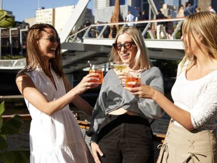 three women toasting cocktails with even walker pedestrian bridge in background