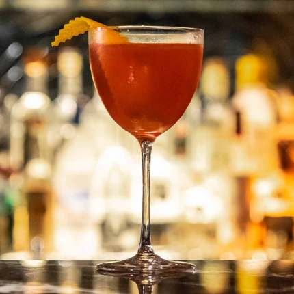 fruit cocktail in tulip glass with lemon zest orange peel