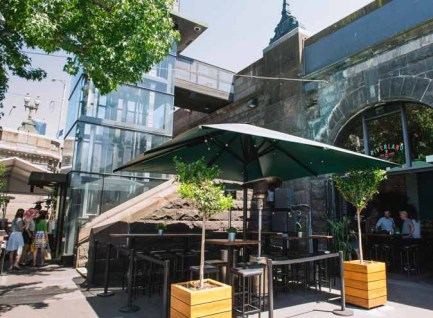 outdoor table and chairs with umbrella and two pot plants at riverland's beer garden