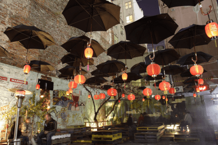 black umbrellas and red chinese lanterns decorating section 8 courtyard bar with brick walls in back ground