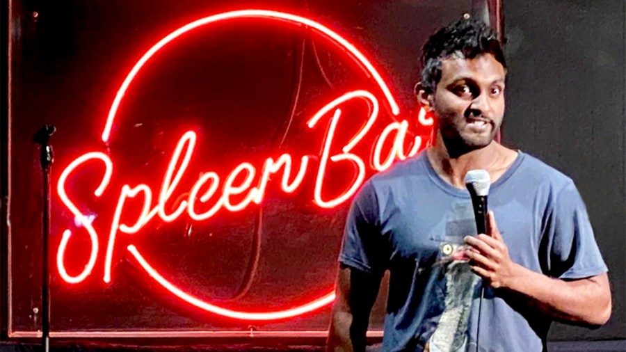 comedian with microphone preforming stand up comedy at Melbourne comedy festival with red neon spleen bar sign