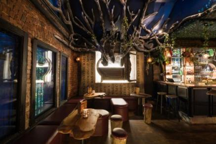 magical tree and vines around upstairs bar seating at storyville melbourne