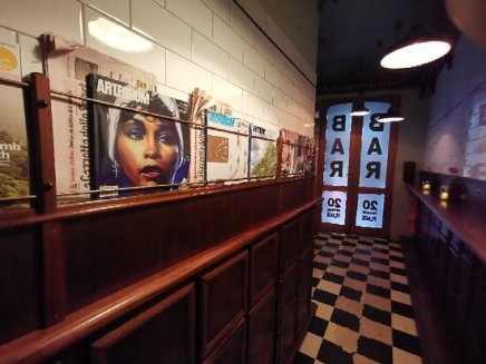 inside bar americano hallway with black and white floor tiles, wooden wall panels and white wall tiles