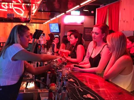 women buying drinks with staff pouring tap bear at barcadia