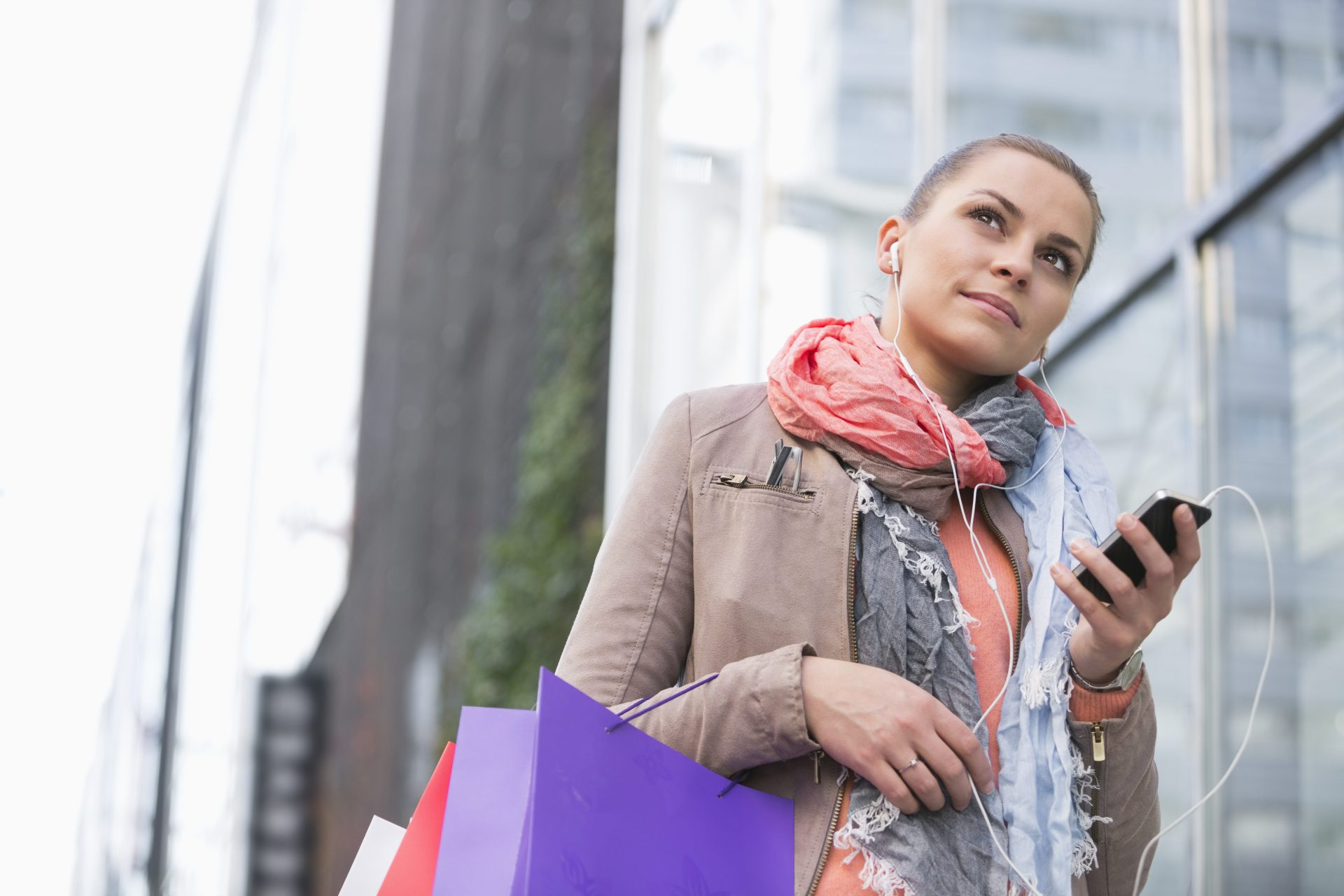 Low angle view of young woman listening to music while shopping