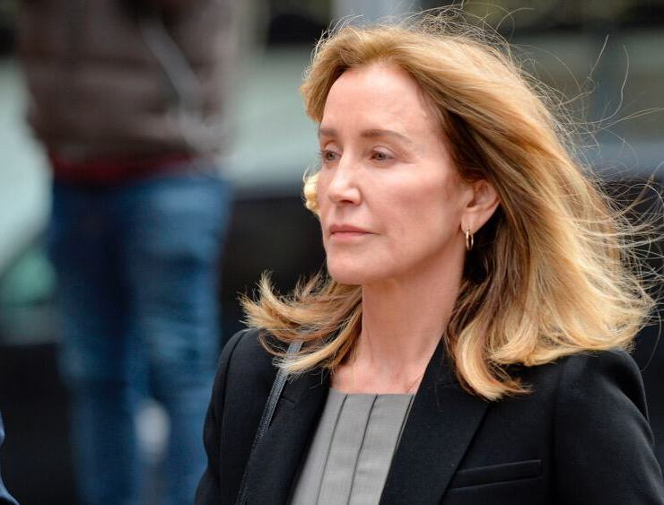 Felicity Huffman is escorted into court