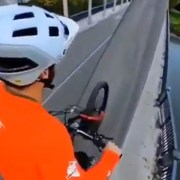 Cyclist bikes over bridge in the most terrifying way