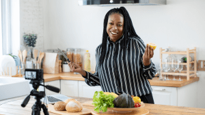 Smiling African American woman vlogger broadcasting a live video cooking demonstration.