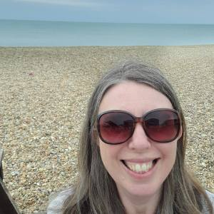 Sarah smiling broadly at the camera. She is wearing large shades, a beach behind her and the ocean beyond that.