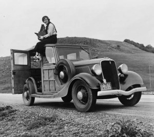 Dorothea Lange, photographer, sits on top of car with her camera