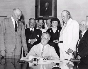 Roosevelt signing Social Security Act of 1935 in the Cabinet Room of the White House. Also shown, left to right: Rep. Robert Doughton (D-NC); Sen. Robert Wagner (D-NY); Rep. John Dingell, Sr. (D-MI); Unknown man in bowtie; Secretary of Labor, Frances Perkins; Senator Pat Harrison (D-MS); Congressman David L. Lewis (D-MD).