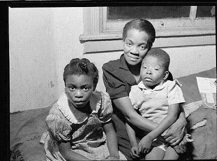 Black family in Chicago who receives relief poses for a picture. Pervasive discrimination, a serious obstacle to very many in need, was present throughout providers of assistance.