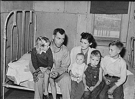 Young family sits together in a cramped living space, a common sight for workers at this time.