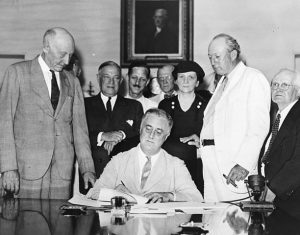 Roosevelt signs into law the Social Security Act, one of Frances Perkins's (standing behind Roosevelt) primary policy initiatives.
