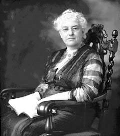 Mary McDowell seated in ornately carved chair. She holds a book in her lap. She wears glasses and her hair is white.