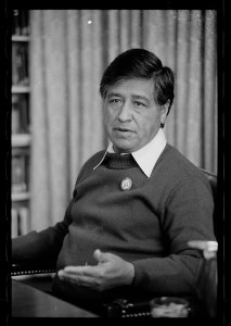 Cesar Chavez, seated for an interview. He wears a pullover sweater. He gestures with his left hand.