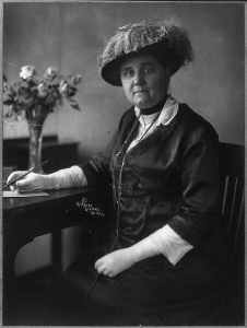 Jane Addams, seated, with pen and paper. She wears gloves and a feathered hat.