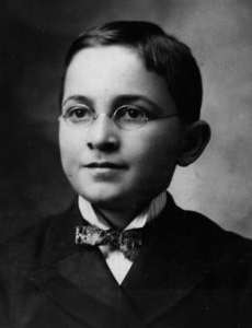 Harry Truman at age 13 wearing a suit, wire-rim glasses, and a neat bow tie.