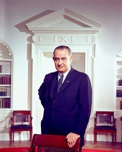 Lyndon B Johnson, one hand behind his back, one hand resting on a chair.
