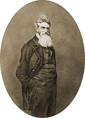 John Brown in 1859 stands with his hands in his pockets. He wears a beard.