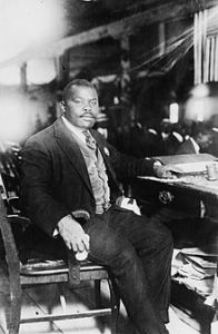 Marcus Garvey seated a a desk.