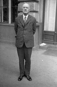 Oswald Parnson Villard stands in front of a building. His hands are clasped behind his back. He wears a suit.