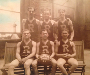 """Basketball Champion Team. Six young men wearing jerseys marked """"R."""" The man in center front holds a basketball saying """"C O A N Champs 30"""""""