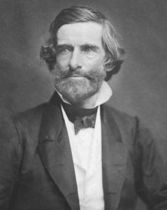 Samuel Gridley Howe. He wears a suit and has long hair and a beard.
