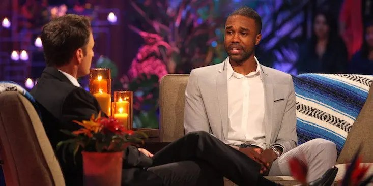 A young Black man sitting on a couch, talking to a TV show host