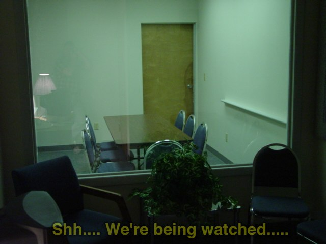 "image of a one-way mirror with caption: ""Shh. We're being watched""."