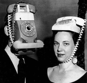 A black and white photo of two people wearing telephones as hats