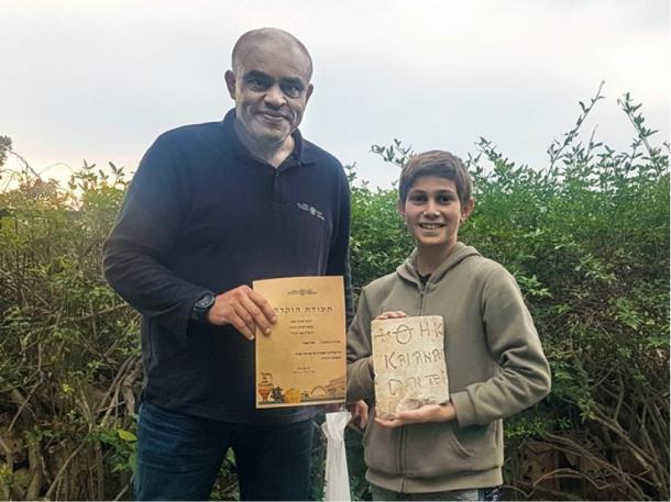 Karem Said, arqueólogo do distrito de Haifa no IAA, concede a Stav Meir um certificado de agradecimento pela descoberta da relíquia bizantina de 1.500 anos de idade perto de Cesareia. (Karem Said / Autoridade de Antiguidades de Israel)