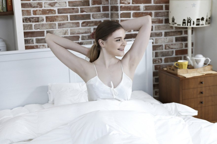 Mulher feliz acordando.