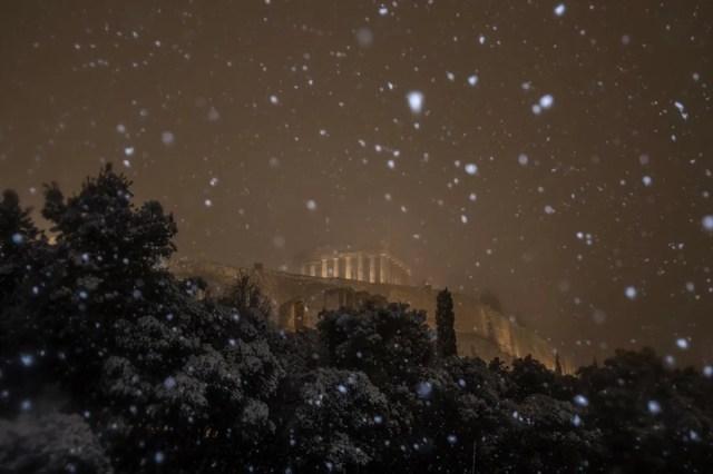 A Acrópole iluminada enquanto a neve cai lá fora