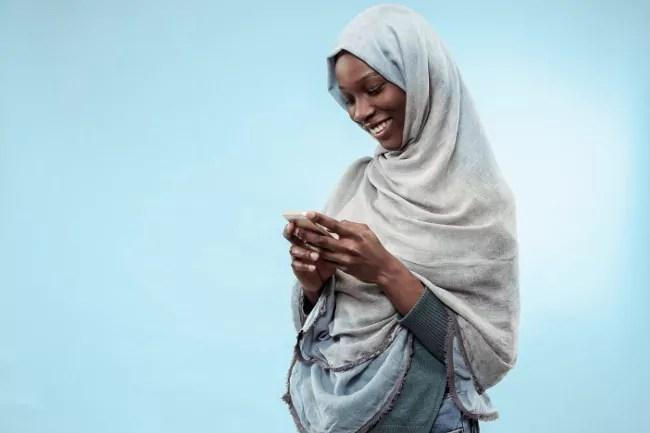 Femme africaine dans un hijab souriant à son smartphone.
