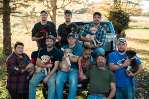 Vicksburg guys hold their Tennessee mutt puppies whom they have made famous. Photo by Britnie Langs Photography.