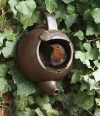 Old teapot turned spout down to make sure any water drains in the garden as a birdhouse