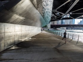 A late afternoon runner passes under a bridge on the Chicago Riverwalk